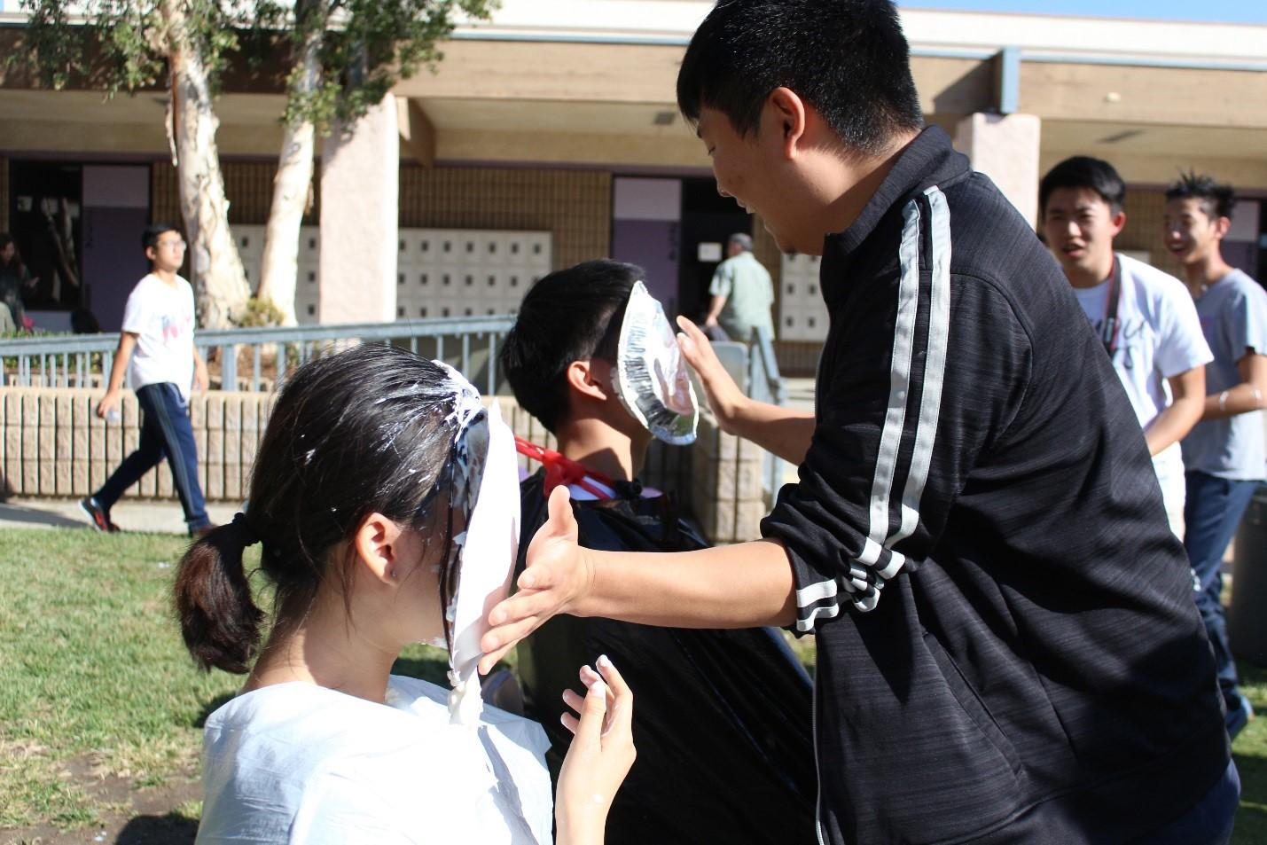 Alumnus Shawn Chae smashes pies in the faces of seniors Melanie Ho and Casey Chen in the event hosted by Red Cross.