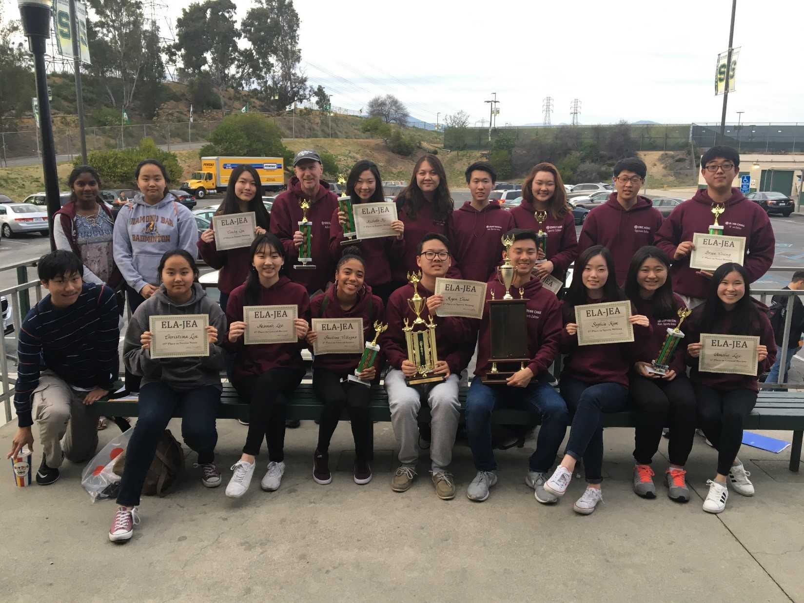DBHS students from Journalism I and The Bull's Eye staff hold up their awards and trophies from the Eastern L.A. JEA write-offs on March 4.