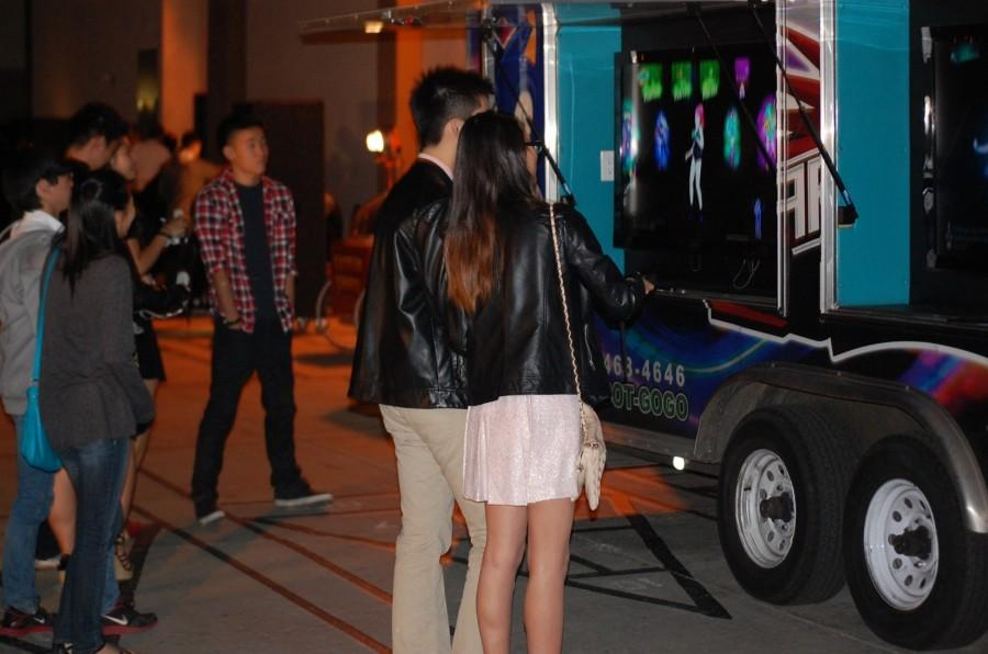 "Sadies attendees Kelley Wu and date Thomas Liu play ""Just Dance"" on a gaming truck in the amphitheater."