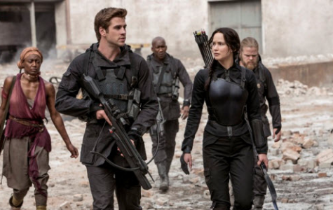 Gale Hawthorne (Liam Hemsworth) accompanies Katniss Everdeen (Jennifer Lawrence) as she sets out to film propaganda films as the symbol of the rebellion, The Mockingjay.