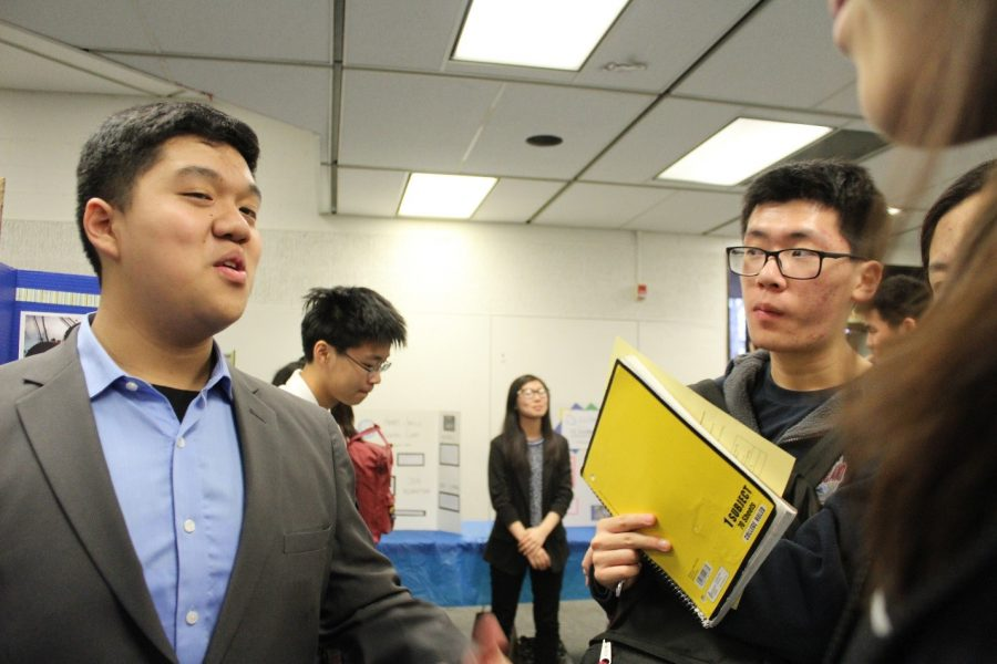 Senior Brahma Tech member Philip Gunadi discusses his Boeing internship experience as junior Kenny Ni looks on.