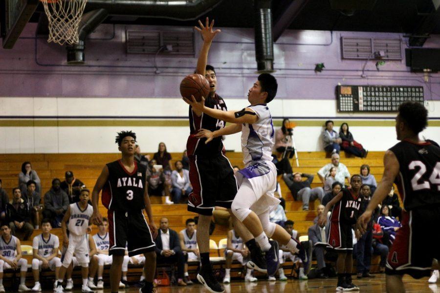 Senior Tyler Tang attempts an acrobatic finish around an Ayala defender.