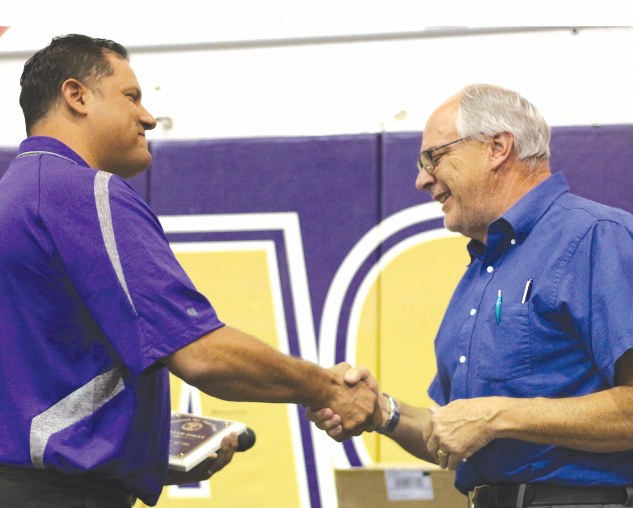 DBHS photography teacher William Foley (right) accepts the Teacher of the Year award from Principal Reuben Jones.