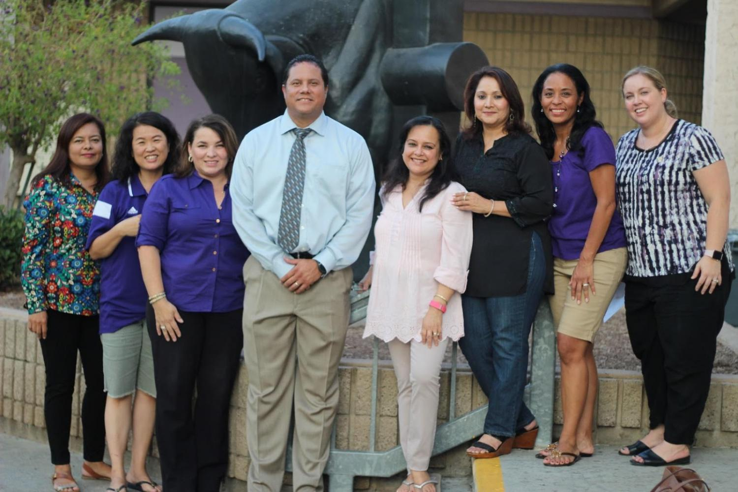 A group of parents, representing the Magnificent Seven, poses at Back to School Night, with principal Rueben Jones.