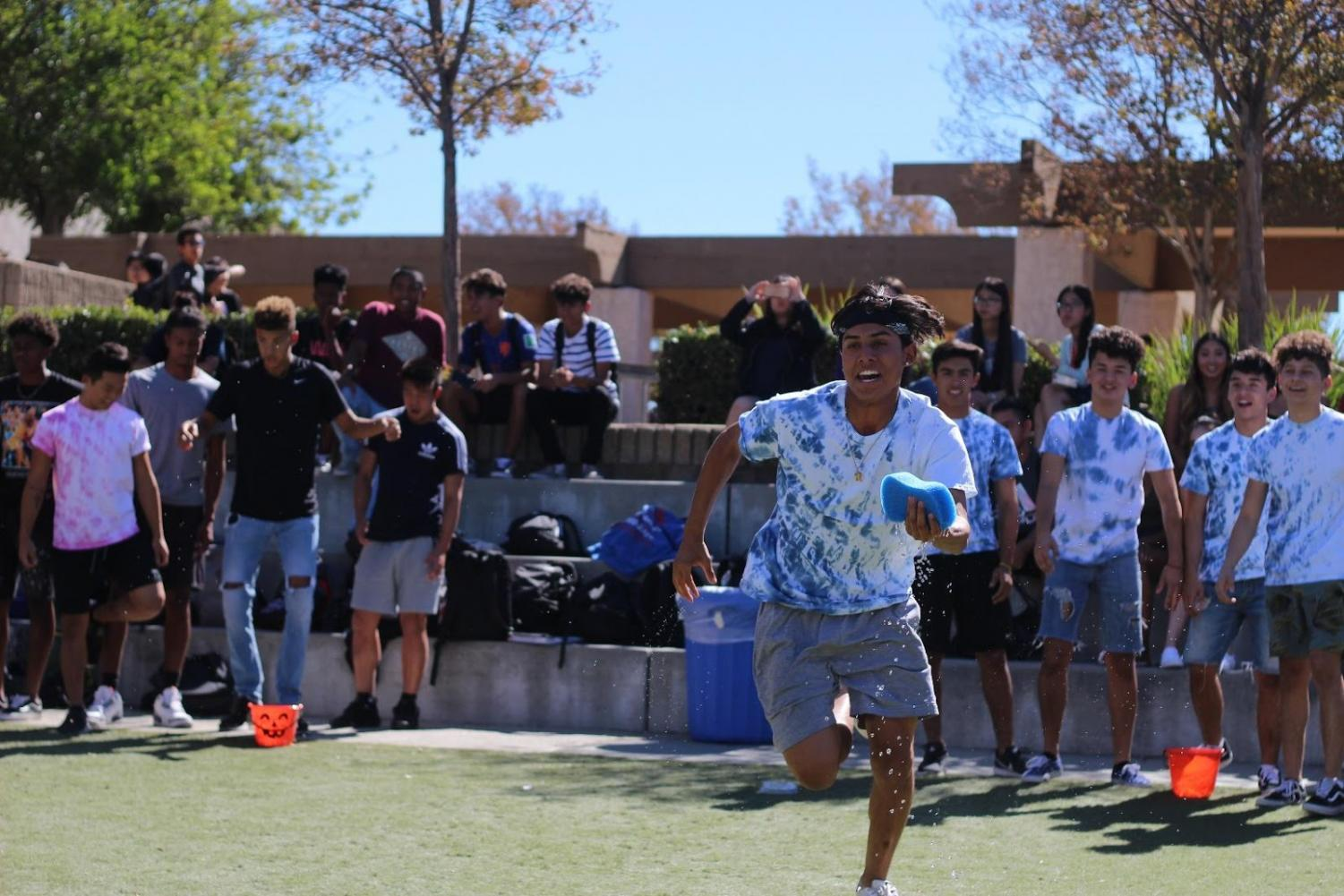 Senior Zack Marin competed for the blue team in the sponge relay as a part of  Rainbow Races in the ampitheater during lunch on Oct. 24.