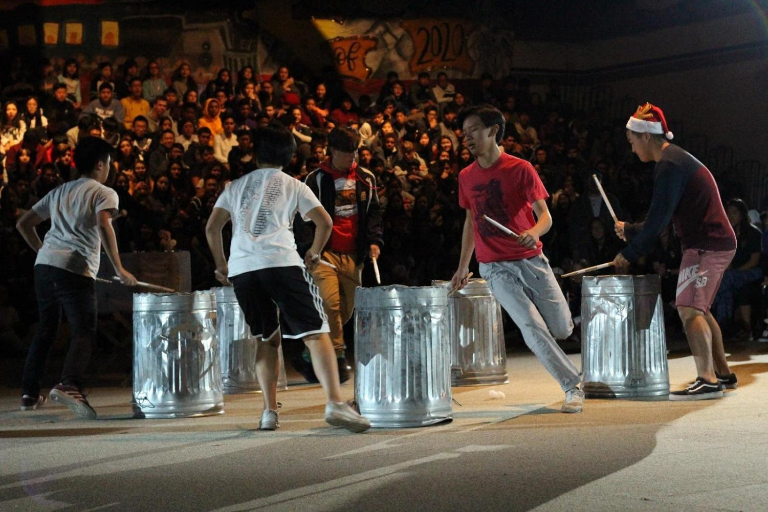 Shown left to right are senior World Line members Edison Chow, Evelyn Lee, Jack May, Isaac Kau and Hyunwoo Kim performing their percussion routine using aluminum trash cans at the winter sports rally on Dec. 8 in the gym.