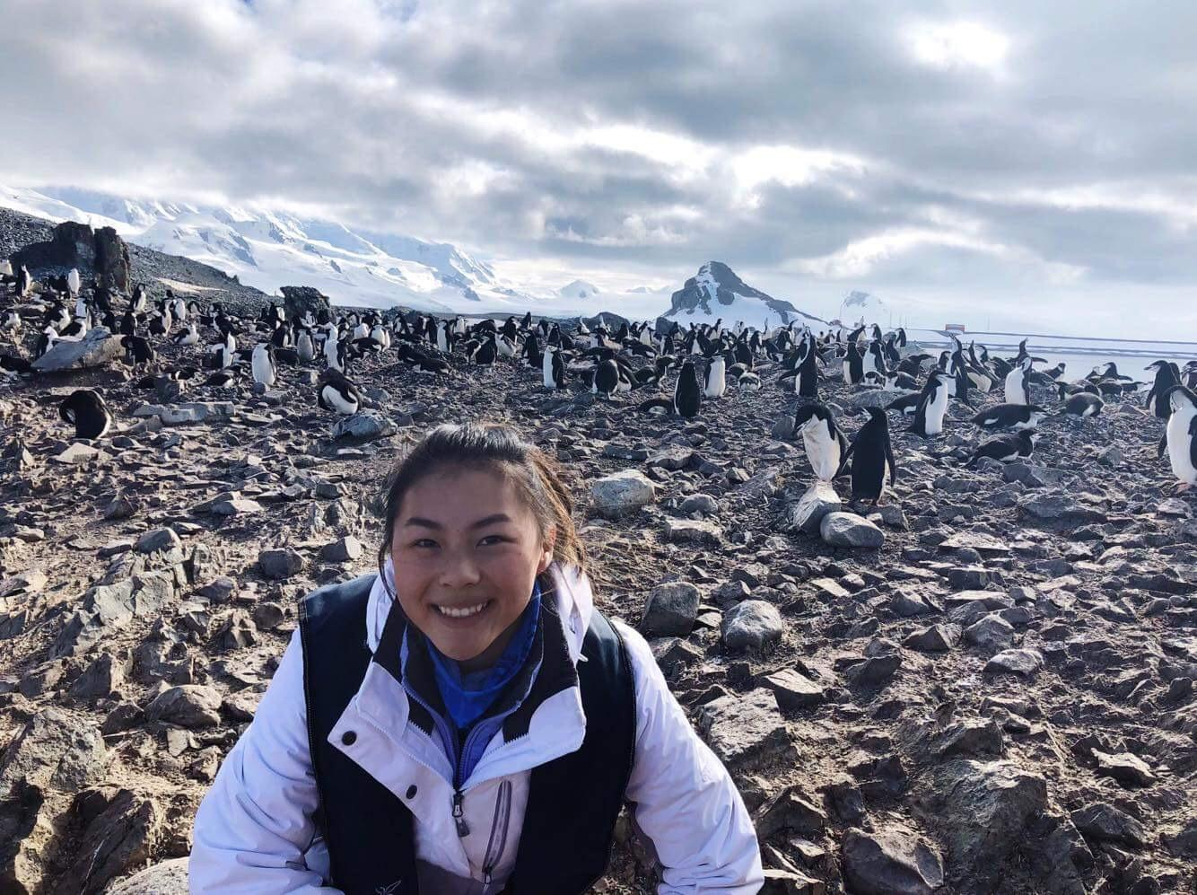 Senior Maria Zhu poses with penguins at Half Moon Island. She visited the continent for six days with a tour group.