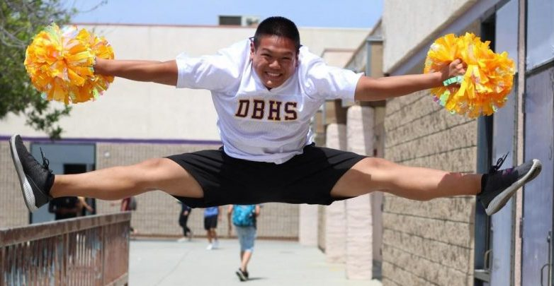 Senior Wesley Lu, the only male cheerleader on the pep team in 17 years, performs a toe touch, a cheerleading stunt.