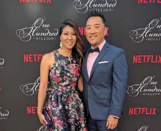 "Alumna Connie Cho (left) poses with her husband for a photo at the red carpet during the""One Hundred Million Subscribers"" celebration for Netflix."