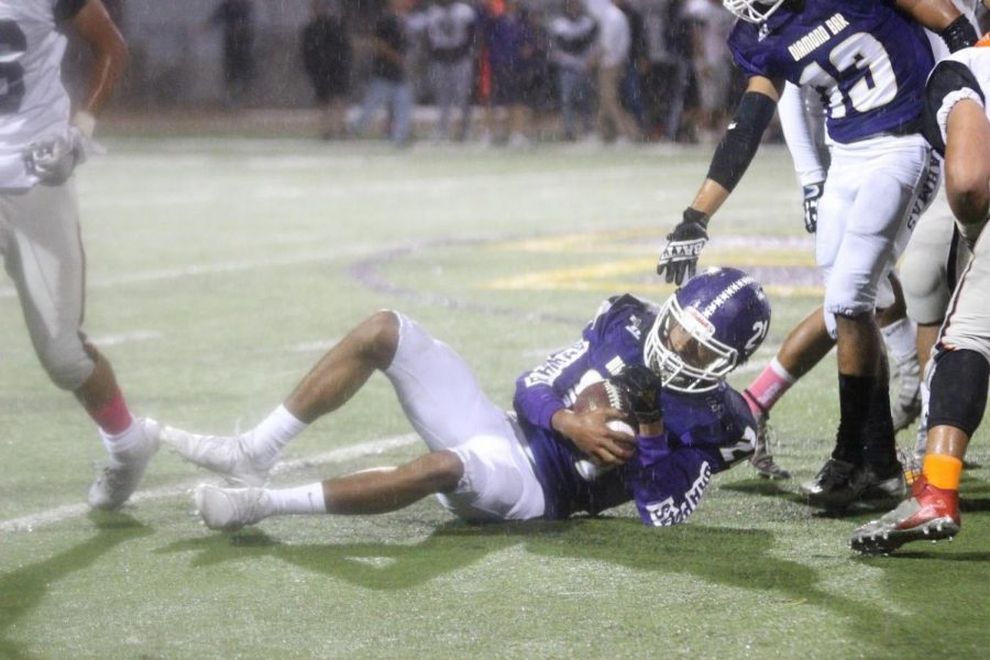 Matthew Uballe secures the ball despite the heavy rain during the first half of their loss against first-seeded Chaffey.