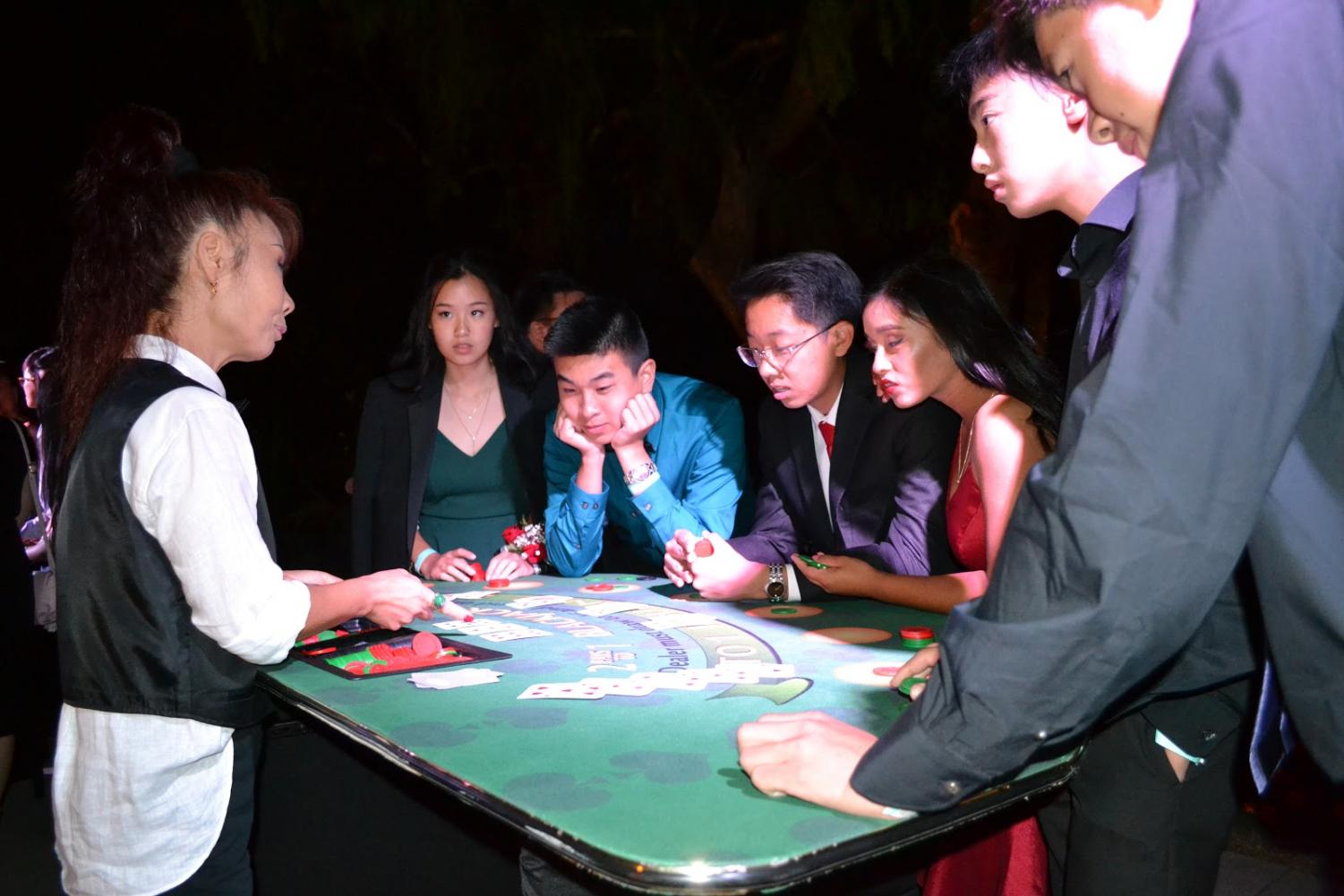 Students at the homecoming dance gather around the Blackjack table