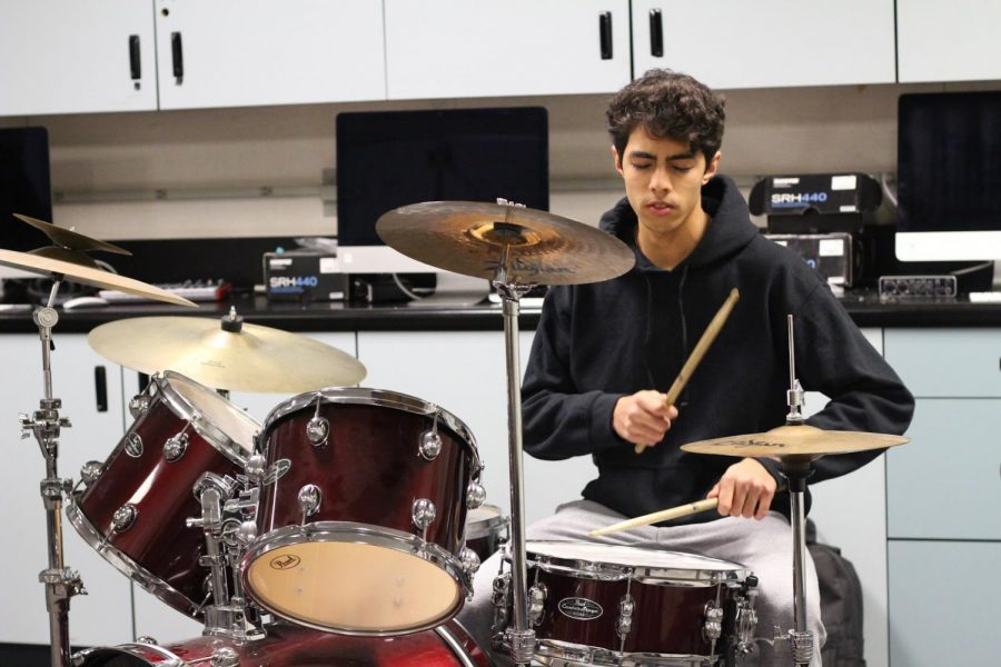 Senior Ryan Shah practicing on a drum set for the upcoming concert.