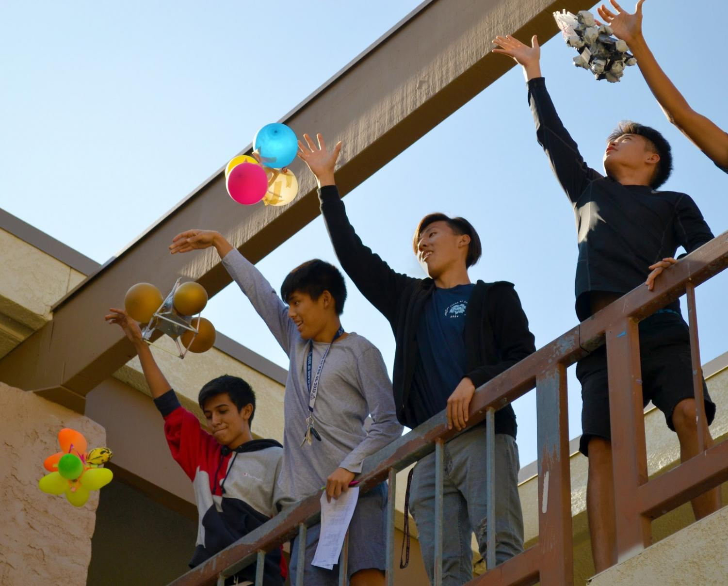 From left, AP Physics students Ernesto Perez, Joshua Park, Royce Park and Colin Park test the ability of their contraptions to protect an egg held inside