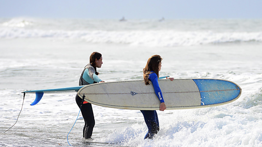 Cathy Lee and her friend charge into the California waves with their surfboards