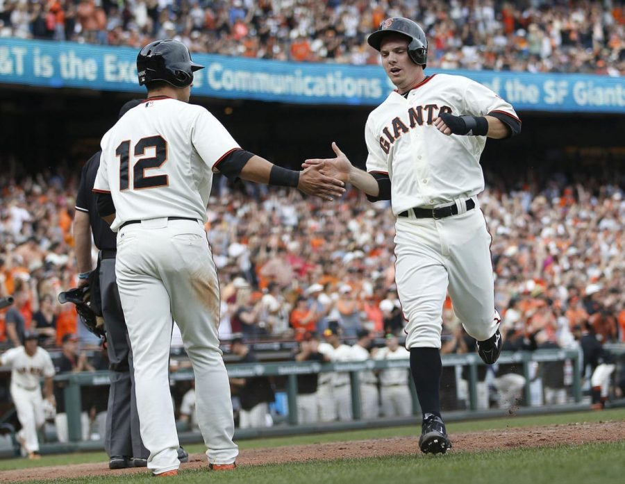 Gary Brown, right, is congragulated by Joe Punik, after scoring in a game against the San Diego Padres in 2015.