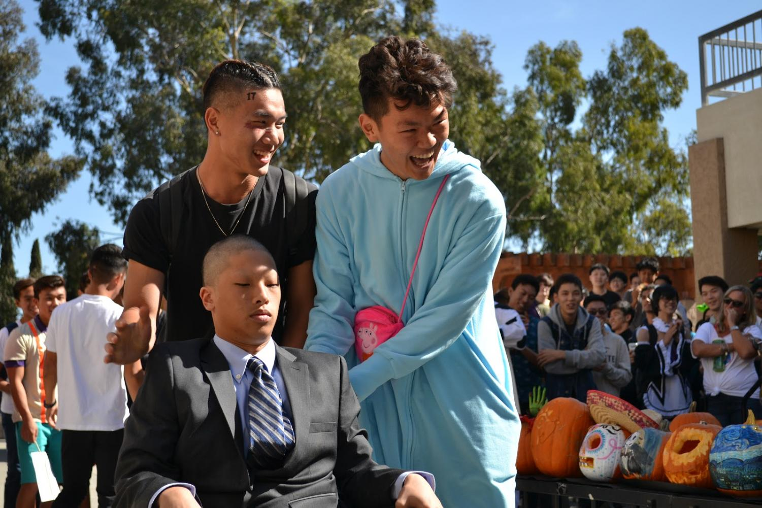 From left, juniors Ricky Kuo, Leo Lu wheel Christopher Lin, dressed as Professor X from the