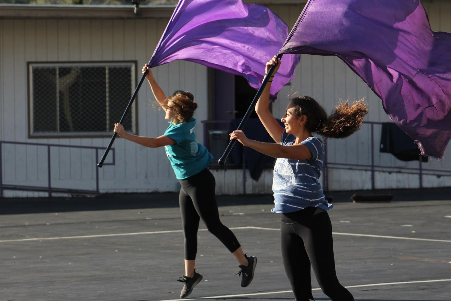 Color guard members practicing with flags during after-school rehearsal