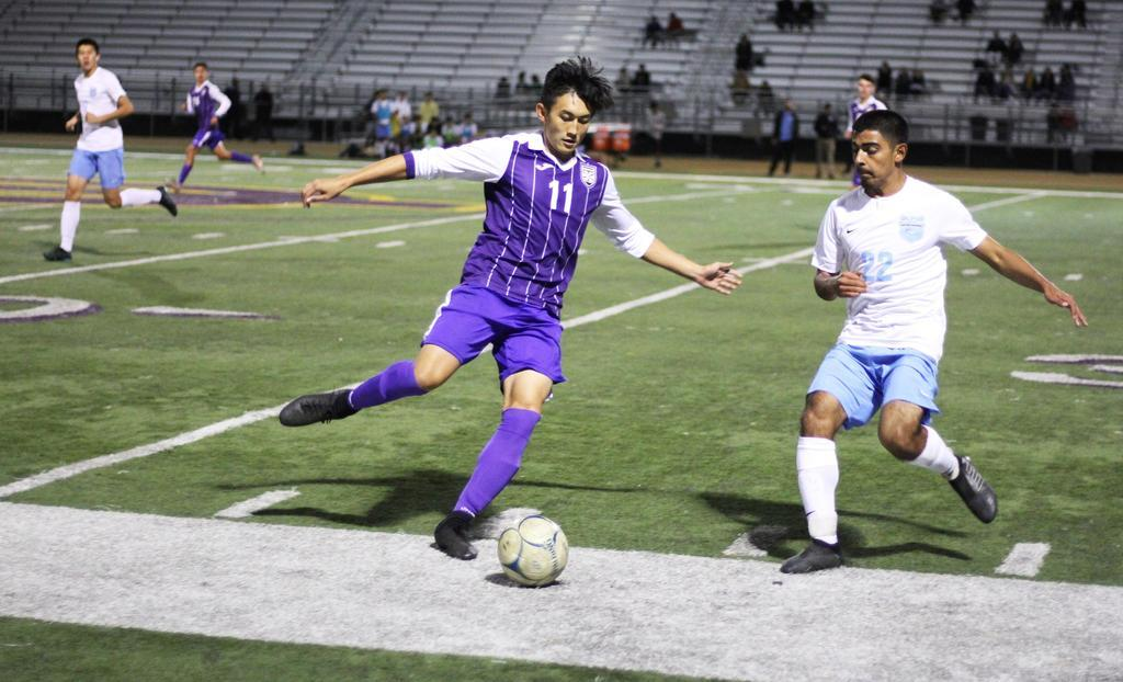 Senior captain Dwight Ritchie attempts to clear the ball in a rivalry game against the Mustangs, where they won 1-0.