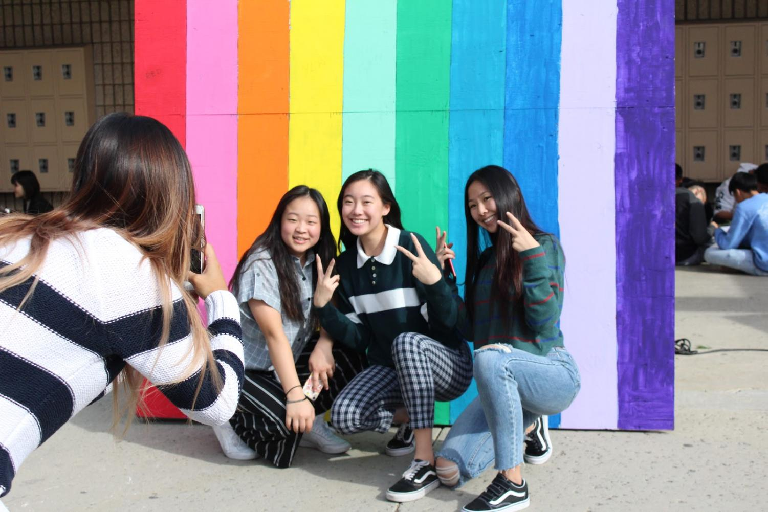 From left, juniors Eunice Sim, Jennifer Nie and Carina Wu pose for a picture before a rainbow backdrop in the upper quad.