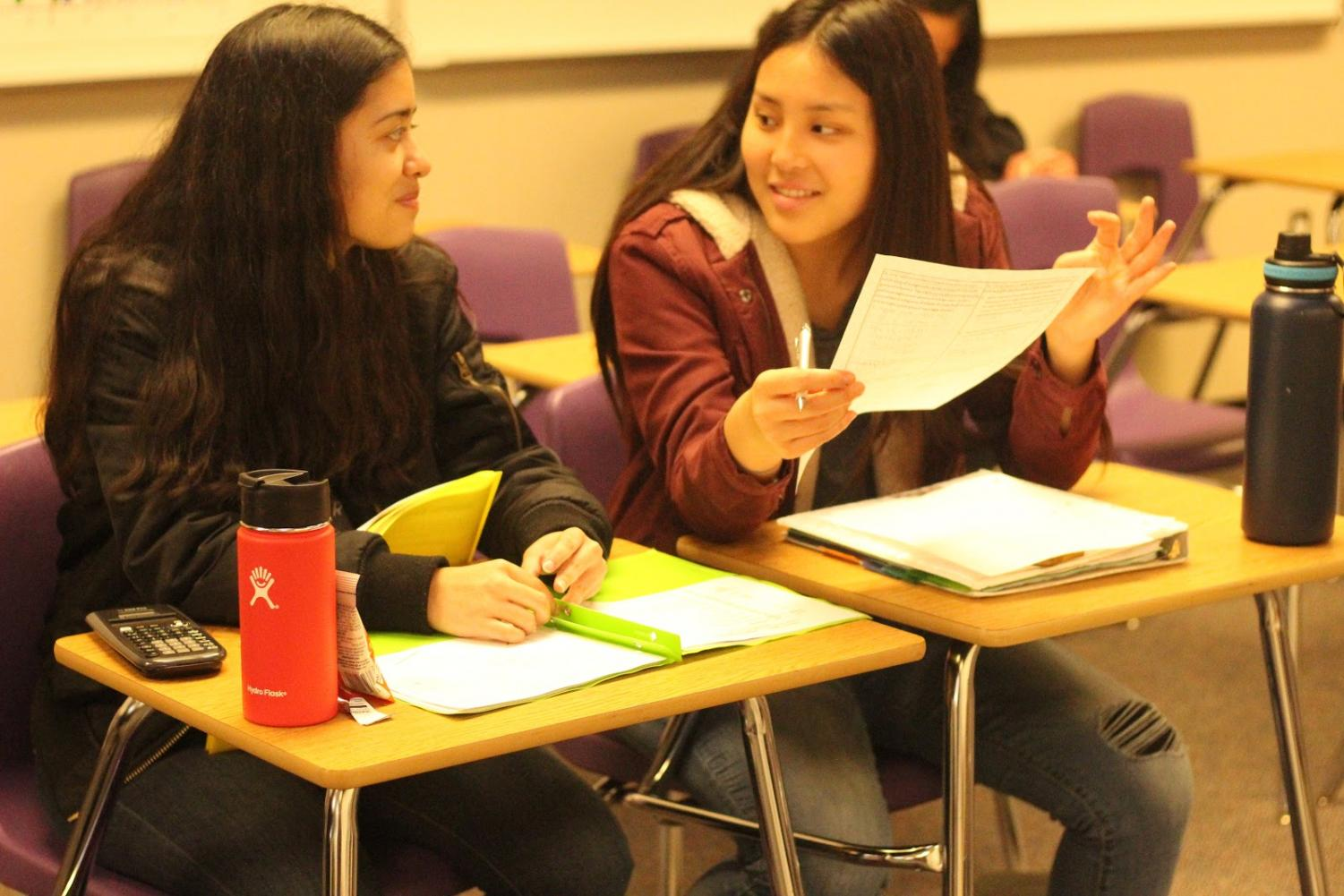 Isabella Garrett, left, and Berince Tang work together on math homework.