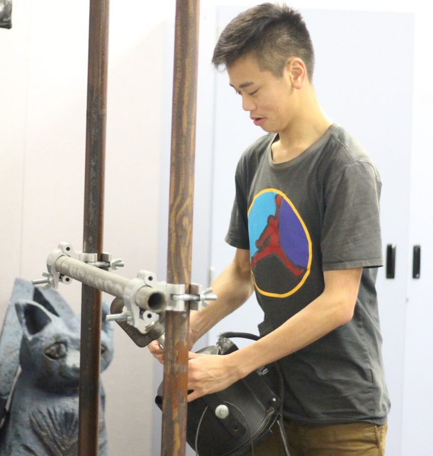 Junior Kenneth Ov constructs a backstage prop in class