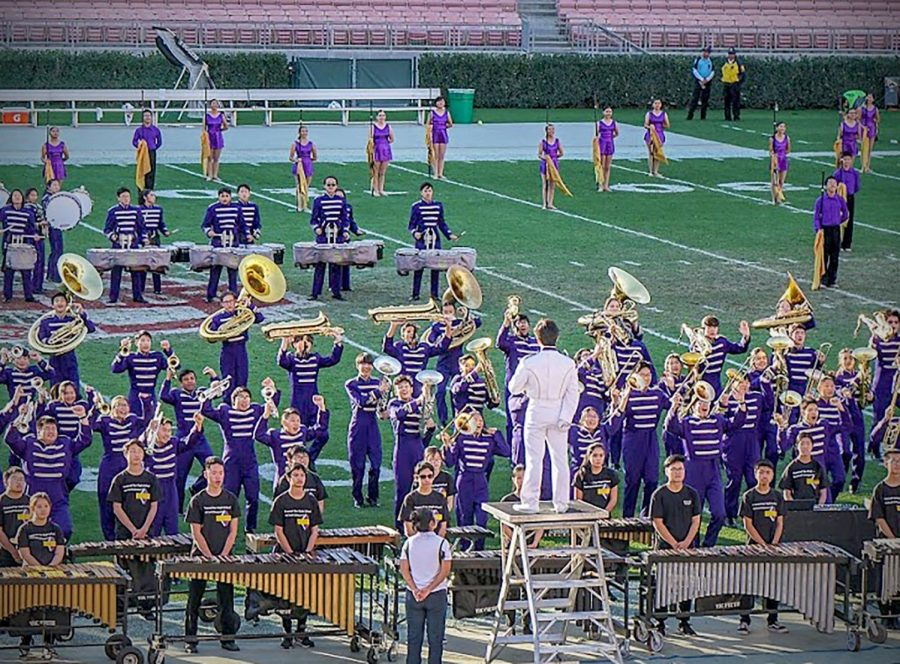 Drum+major+Aaron+Tamura+stands+overhead+as+drumline%2C+marching+band+and+color+guard+perform+their+show+on+the+Rose+Bowl+football+field+last+weekend.%0A%0A