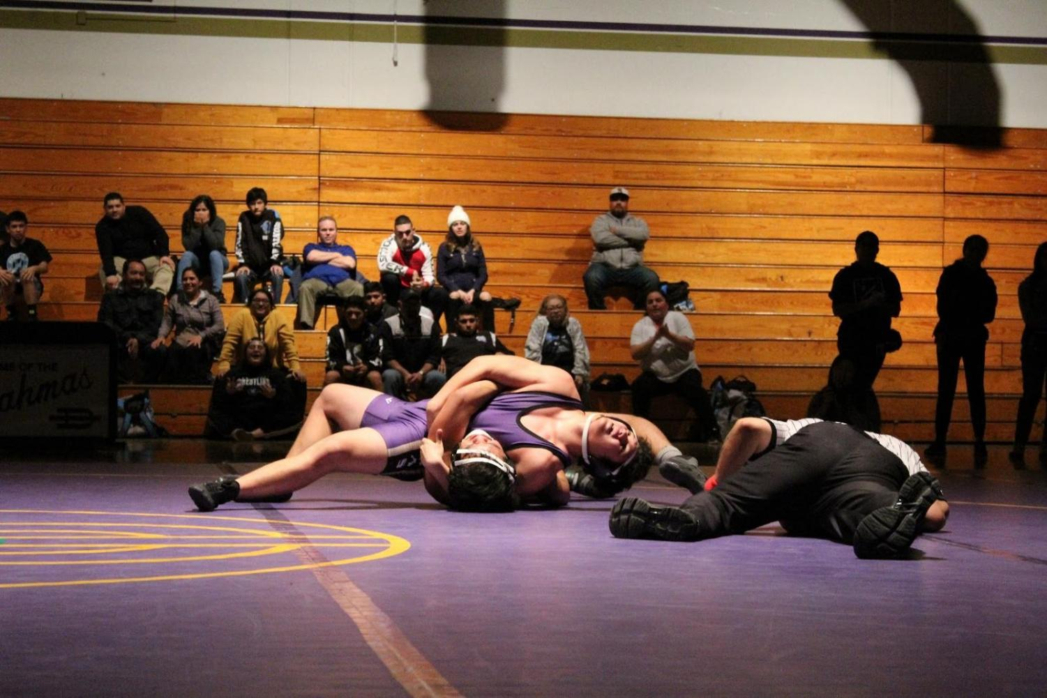 Senior Antonio Diones pins his opponent during the last match of the season.