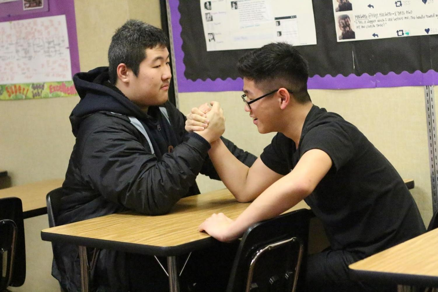 Junior Jack Che, left, and freshman Isaac Chung arm wrestle during lunch. The club meets every Wednesday to compete against each other.