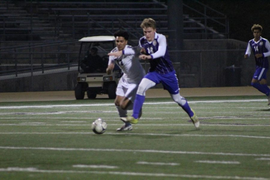 Senior Zachary Daniels struggles for the ball in the team's second league win; the boys finished the season tied for third.