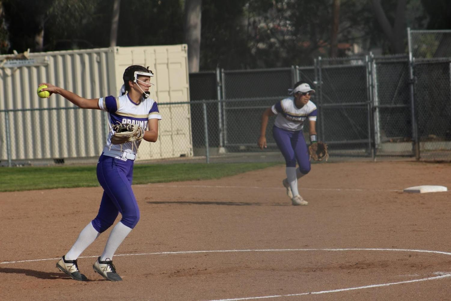 Sophomores Miranda Montes pitches while Carina Sanchez scans the outfield.