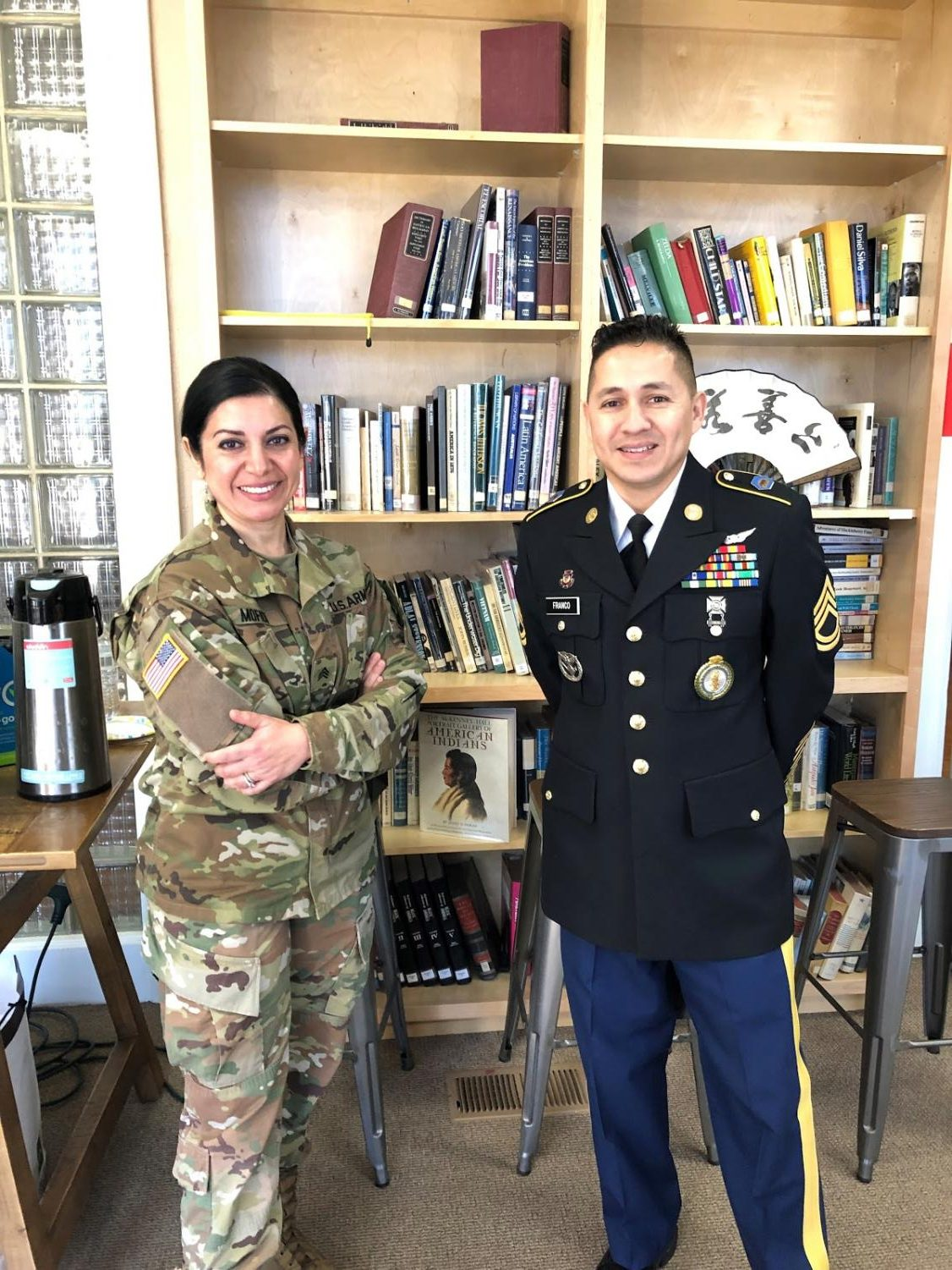 Alumnus Carlos Andres Franco, right, wears his uniform as he poses with a colleague on Pomona Catholic career day.
