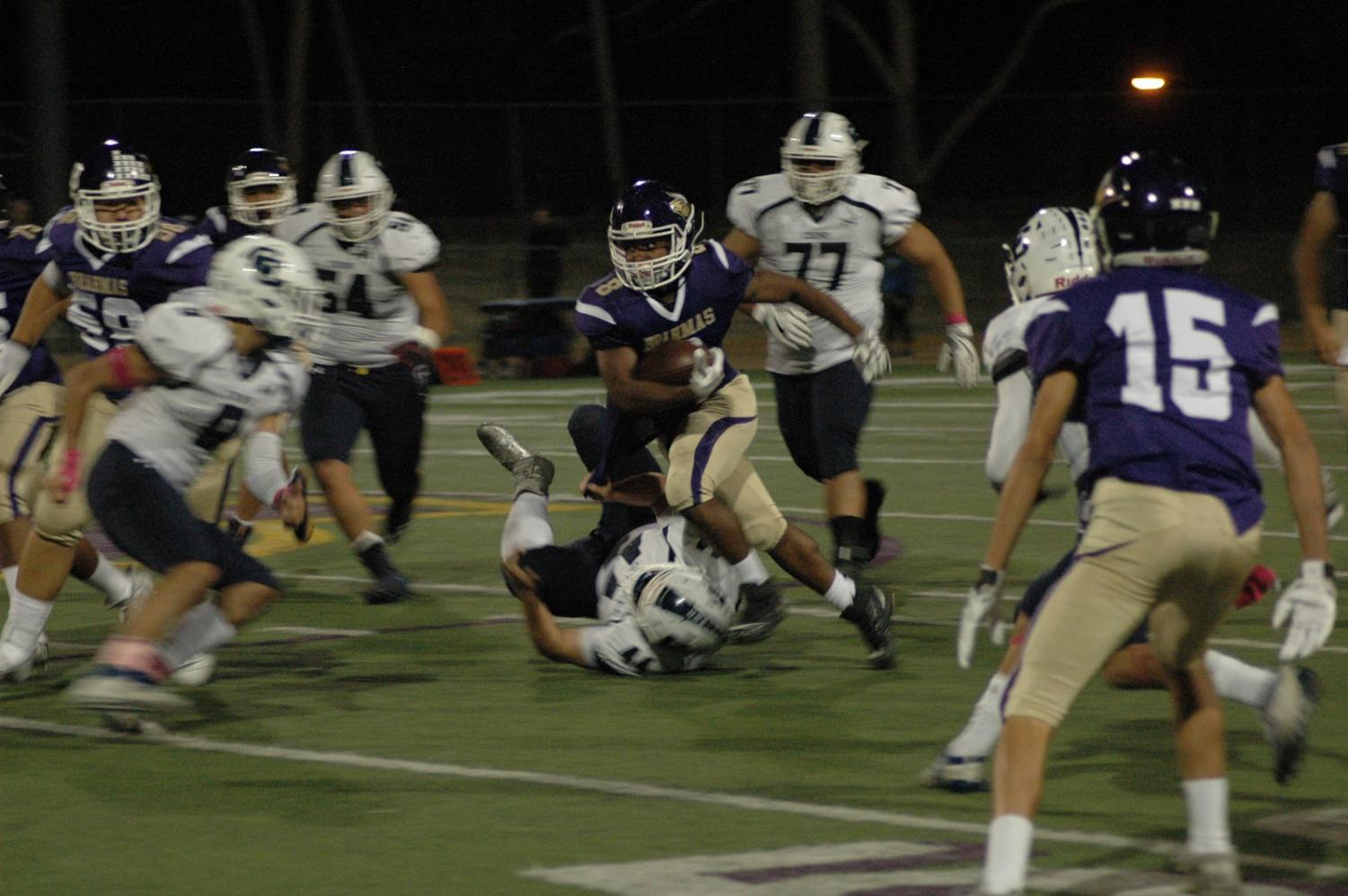 Junior Josiah Hunter runs by the defense at the Homecoming game.