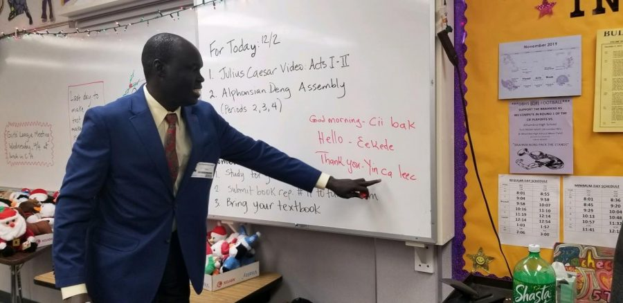 "Author Alephonsion Deng, who shared his experience as a Lost Boy of Sudan with students on Dec. 2, shows how to say ""Thank you"" in his native language."
