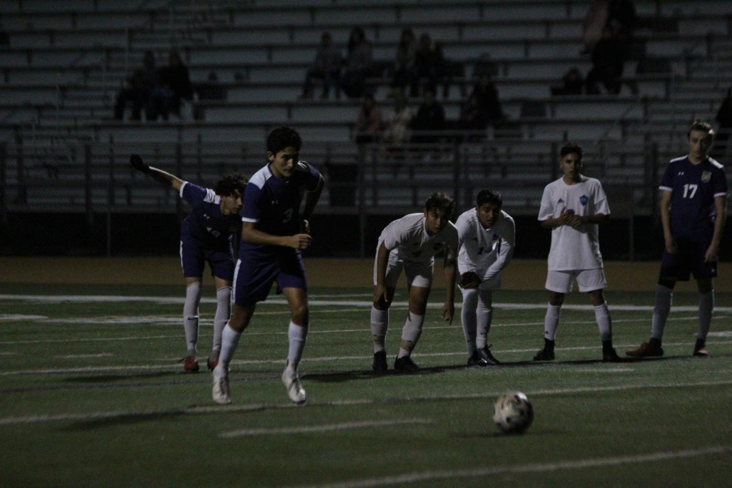 Junior Jayden Sanchez goes in for a penalty shot against Chino High School while teammates anticipate a scored goal.