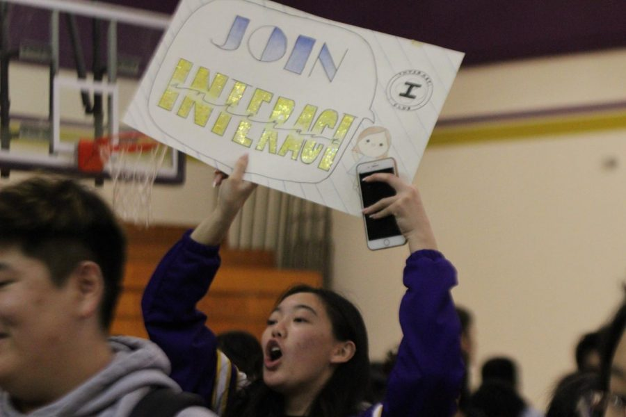 Senior Jennifer Nie holds up a poster for the Interact Club during the Jan. 23 event.