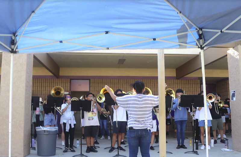 Music director Marie Santos of the Thundering Herd marching band guides the brass section in rehearsal of a performance.